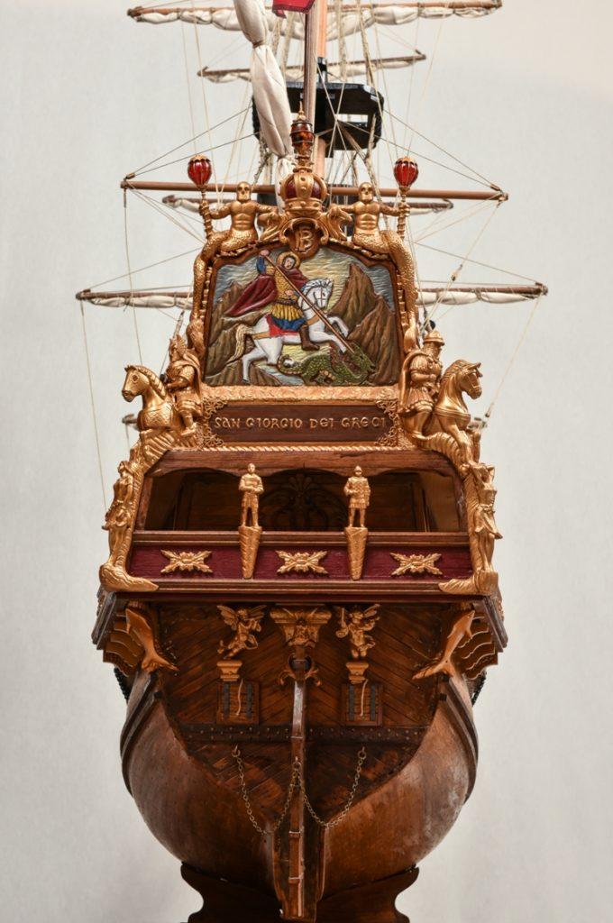 Η περίτεχνα διακοσμημένη πρύμνη του πλοίου όπου στον « καθρέφτη » της  δεσπόζει ο πολεμιστής Αγ. Γεώργιος των Ελλήνων ( San Giorgio dei  Greci)  πλαισιωμένος από δύο ξυλόγλυπτους  έφιππους  πολεμιστές. Ο « καθρέφτης » της πρύμνης αποτελούσε στα γαλιόνια τον χώρο όπου τοποθετούσαν τον Εθνικό η προσωπικό θυρεό του βασιλιά, του άρχοντα η του πλοιοκτήτη του πλοίου.