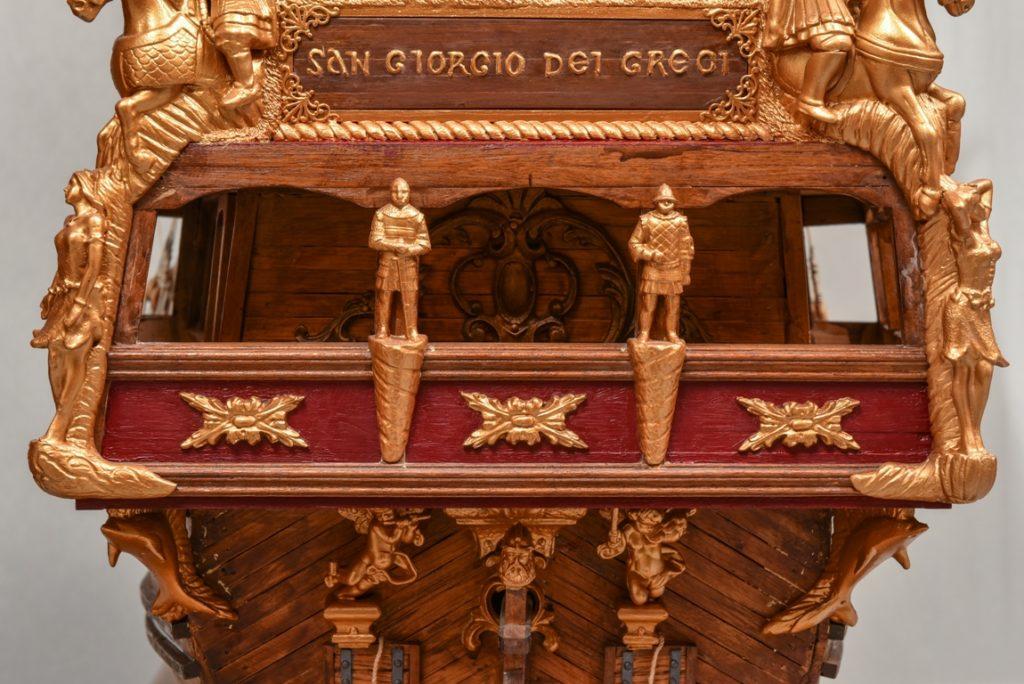 Το πρυμναίο  μπαλκόνι – εξώστης του πλοίου διακοσμημένο με περίτεχνες ξυλόγλυπτες μορφές νυμφών και μεσαιωνικών πολεμιστών. Πάνω από την οροφή του διακρίνουμε ανάγλυφο με χρυσά γράμματα τ όνομα του πλοίου.