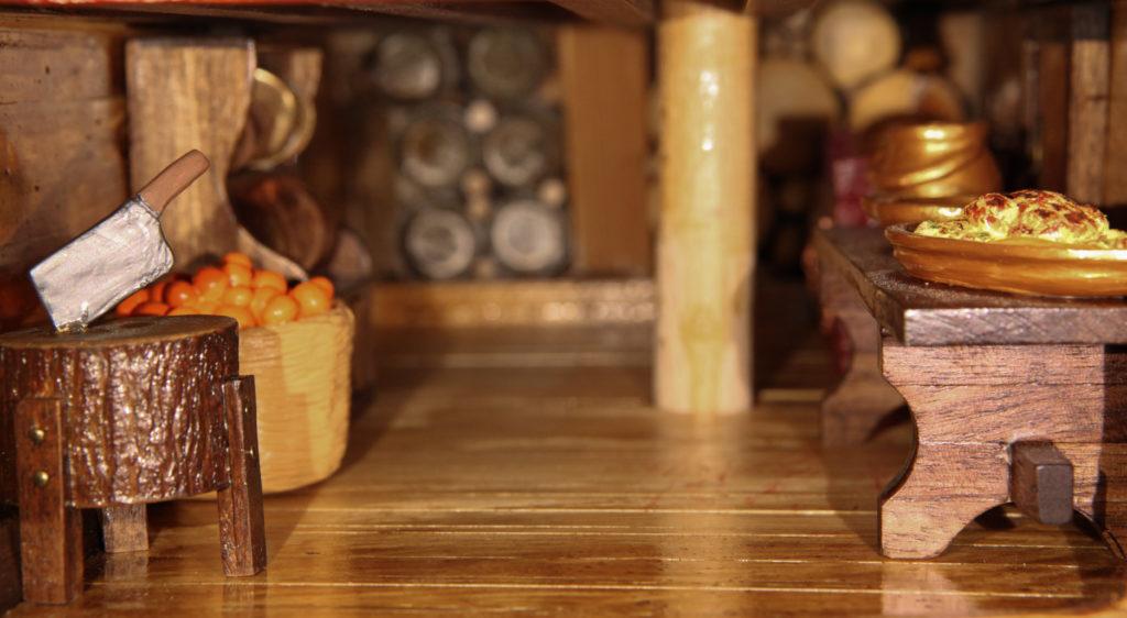 Η κουζίνα του πλοίου με τον φούρνο μαγειρέματος, τραπέζι με φαγητά , μαγειρικά σκεύη, καλάθι με φρούτα, για την καταπολέμηση του Σκορβούτου,  ραφιέρα με πιατικά και το κούτσουρο με τον μπαλτά που έκοβαν τις μερίδες.